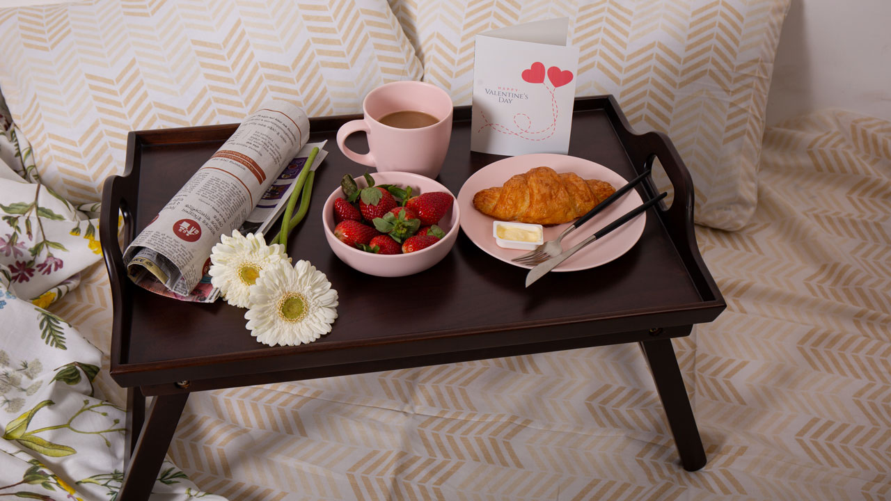 A beautiful breakfast, flowers and a newspaper arranged on a wooden tray
